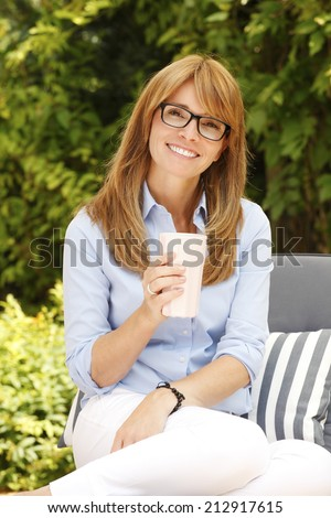 Portrait of part time business woman with mug relaxing at garden, while working at home. Small business. - stock photo