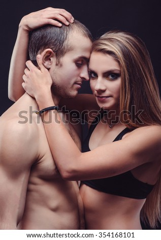 Portrait of passion couple in dark. Woman hug her man.