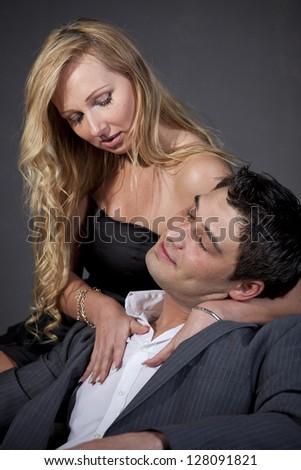 Portrait of passionate couple in studio over grey - stock photo