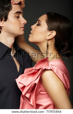 Portrait of passionate couple looking at one another on black background - stock photo