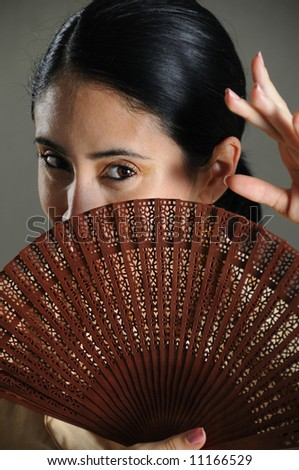 Portrait of passionate flamenco dancer girl covering her face with traditional fan - stock photo