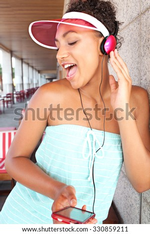 Portrait of passionate retro african american teenager girl listening to music with her smartphone and headphones, singing during a summer colorful day, outdoors. Technology lifestyle, exterior. - stock photo