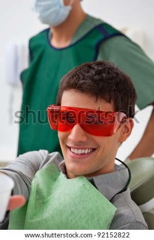 Portrait of patient at dental clinic with dentist standing in background
