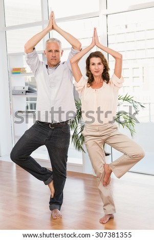 Portrait of peaceful casual business colleagues doing yoga in the office - stock photo