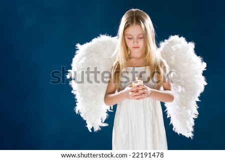 Portrait of peaceful girl wearing white wings looking at candle in her hands over blue background - stock photo