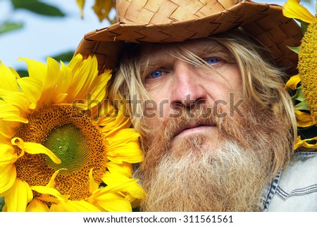 portrait of peasant in a field of sunflowers in summer day - stock photo