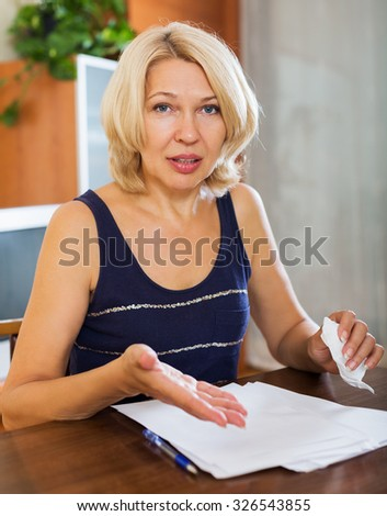 Portrait of  pensioner reading documents at the table in home or office