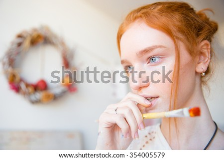 Portrait of pensive beautiful young female holding paintbrush and thinking - stock photo