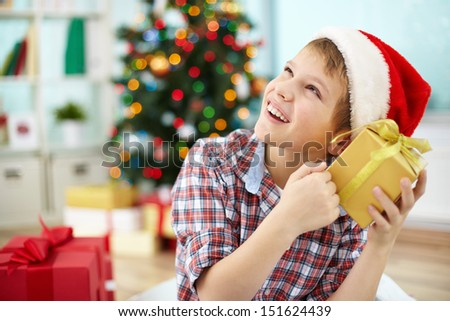 Portrait of pensive boy holding giftbox and guessing what is inside on Christmas evening
