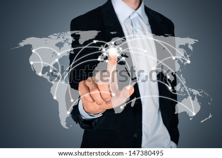 Portrait of pensive handsome businessman touching a world map on the screen showing global connection between different continents. Isolated on dark gray background - stock photo