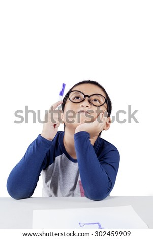 Portrait of pensive male elementary school student thinking idea while holding a pen, isolated on white background - stock photo