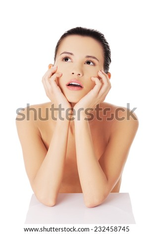 Portrait of pensive nude woman with hands on chin. - stock photo