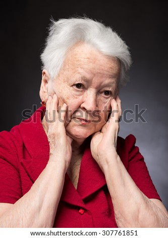 Portrait of pensive old woman on a grey background - stock photo
