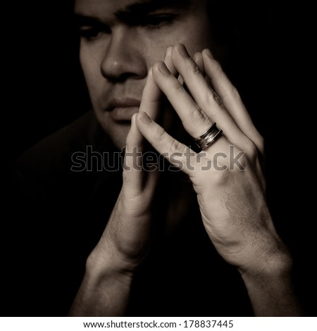 Portrait of pensive, sad, serious man with hands, studio