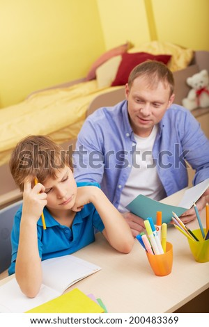 Portrait of pensive schoolboy and his father making schoolwork at home - stock photo