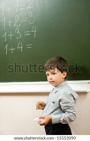 Portrait of pensive schoolchild standing at blackboard and doing sums