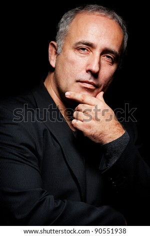 portrait of pensive senior man over black background