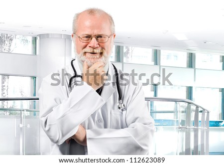 Portrait of pensive senior medical doctor isolated over clinic background - stock photo