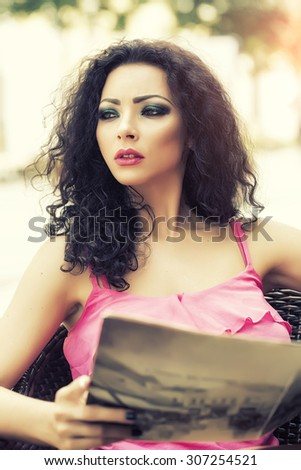 Portrait of pensive sexual young woman with brunette curly hair and bright makeup looking away holding magazine sitting outdoor on wattled chair, vertical picture - stock photo