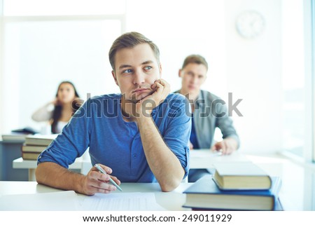 Portrait of pensive student carrying out test - stock photo