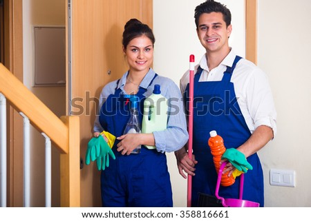 Portrait of people in overalls with supplies ready for cleaning in doorway - stock photo