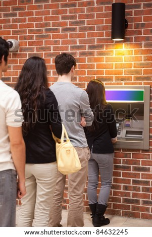 Portrait of people queuing to withdraw cash at an ATM - stock photo