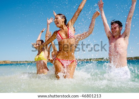Portrait of people splashing on each other in the lake