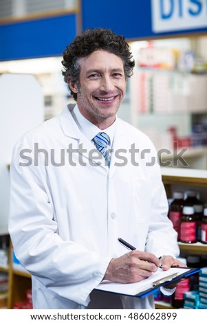 Portrait of pharmacist writing on clipboard in pharmacy