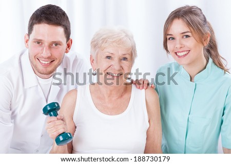 Portrait of physiotherapists and exercising elderly woman