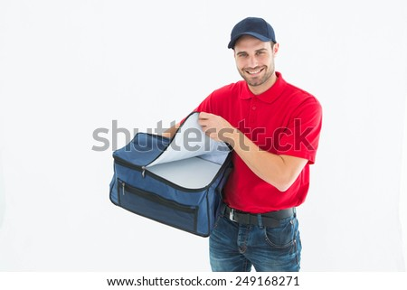 Portrait of pizza delivery man opening bag on white background - stock photo