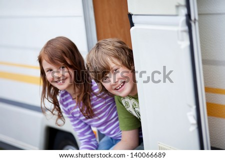 Portrait of playful boy and girl sitting at caravan entrance - stock photo