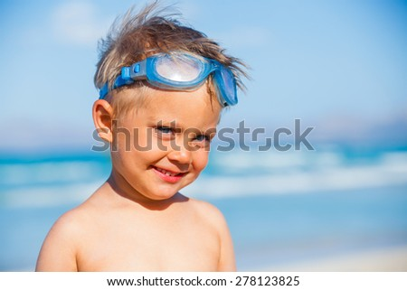 Portrait of playful boy in swimming goggles on the beach with sea on background - stock photo