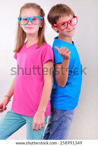 portrait of playful brother and sister twins with sunglasses having fun - stock photo
