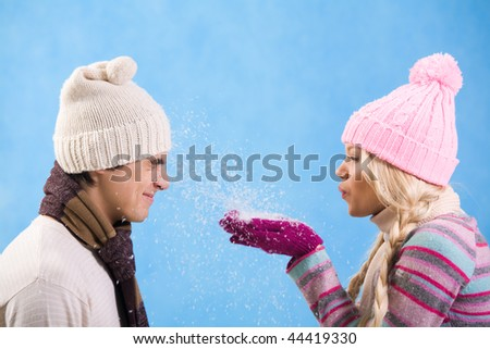 Portrait of playful girl in warm clothes blowing snow onto guy face
