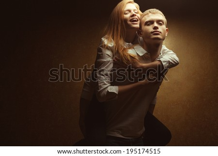 Portrait of playful red-haired (ginger) fashion twins in casual shirts and posing over golden background together. Boy holding girl over his back. Hipster style. Copy-space. Studio shot - stock photo