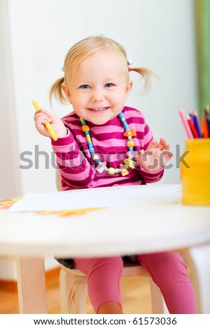 Portrait of playful toddler girl drawing with pencils - stock photo
