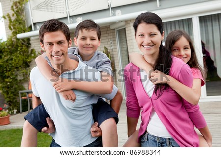 Portrait of playful young family enjoying together outside their home - stock photo