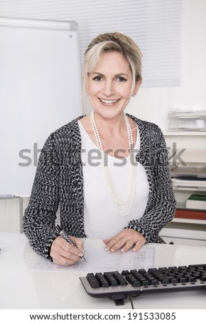 Portrait of pleased smiling mature business woman sitting at desk at office. - stock photo