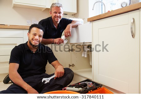 Portrait of plumber with apprentice in domestic kitchen - stock photo
