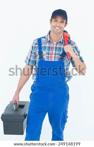 Portrait of plumber with monkey wrench and tool box over white background - stock photo
