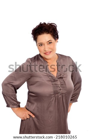 Portrait of Plus Size Woman with Short Hair Standing with Hands on Hips Against White Background - stock photo