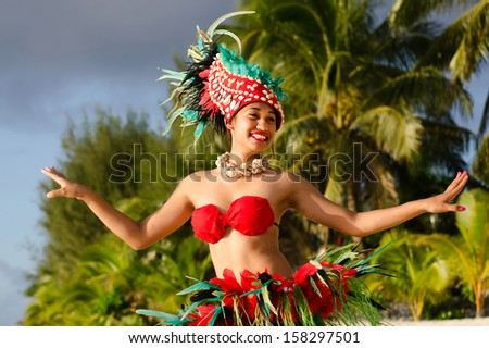 Portrait of Polynesian Pacific Island Tahitian female  dancer  in colorful costume dancing on tropical beach with palm trees in the background. - stock photo