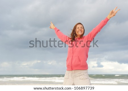 Portrait of positive and happy mature woman at the beach, wearing pink sweater, isolated with ocean and storm clouds as background and copy space. - stock photo