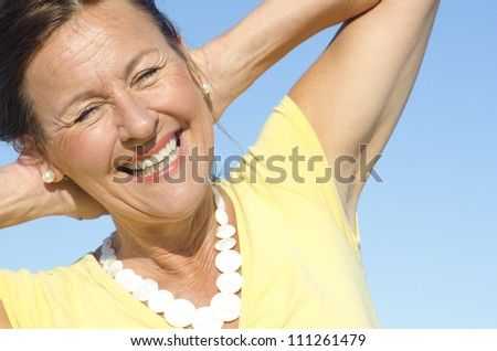 Portrait of positive and optimistic attractive senior woman with arms behind neck, isolated with blue sky as background and copy space. - stock photo