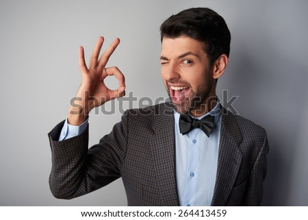 Portrait of positive casual young man wearing jacket and bow tie. Man smiling, winking and showing ok sign - stock photo