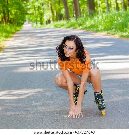 Portrait of positive crazy cheerful girl on roller skates. Young woman in roller skates. happy young brunette woman rides on roller skates in the park and falls - stock photo