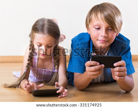 Portrait of positive kids playing with smartphones in domestic interior
