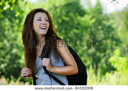 Portrait of positive laughing dark-haired girl looking back, wearing grey t-shirt and black backpack at summer green park. - stock photo