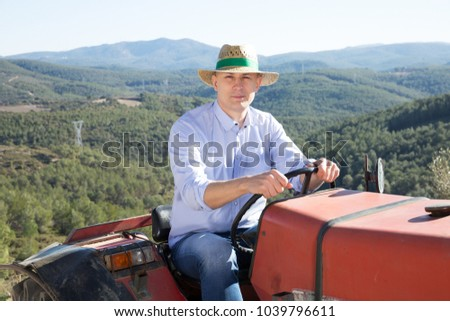 Portrait of positive male in straw hat sitting on tractor on background with vineyard