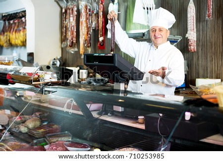 Portrait of positive mature male seller posing with wursts in butchery